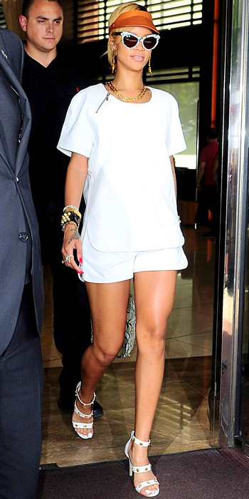 071613-rihanna-350Rihanna weathered the heat in a crisp white tee and shorts, a neutral visor, white cat-eye sunnies, gold jewelry (plus, a stack of bracelets) and studded white Versace heels.
