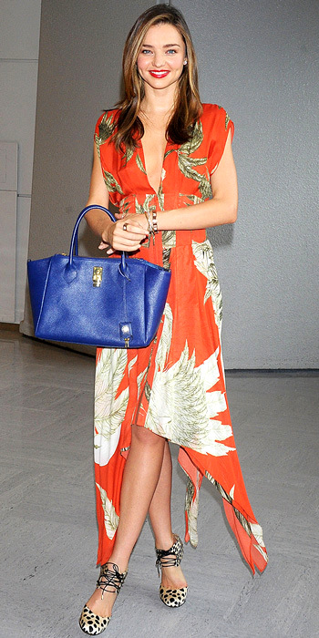 071913-miranda-kerr-350aKerr de-planed at the Narita International Airport in style, wearing a plunging printed orange Wes Gordon dress, blue leather bag and Bionda Castana leopard print heels.