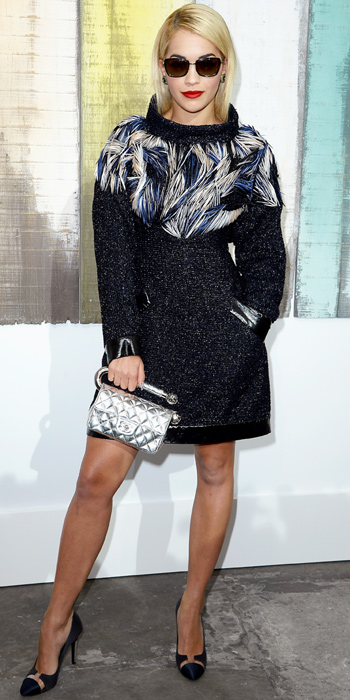 100113-Rita-Ora-350Also sitting in the front row at Chanel, Ora went for a dramatic look, opting a tweed Chanel dress with multicolored feather appliques. For accessories, she clutched a silver quilted clutch an
