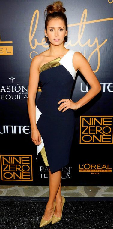 The Top Notch Stylish Look: Goes To Nina Dobrev With That Trendy Hair Style & Her Take On A Asymmetrical Navy & White With Gold Accents Dress By Andrew Gn At The Nine Zero One Salon Melrose Place Launch Party In Los Angeles.