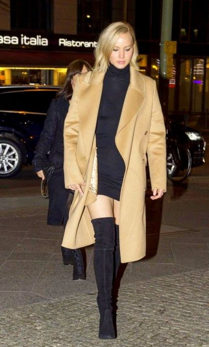 Jennifer Lawrence wears a black minidress, camel coat, and thigh-high suede boots