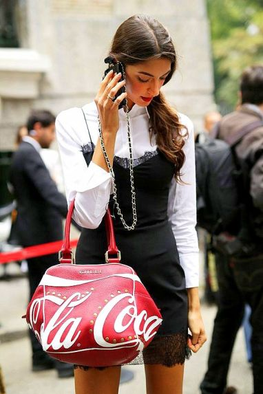 A lace slipdress gets an upgrade with a chainstrap phone case and a touch of Coca-Cola.
