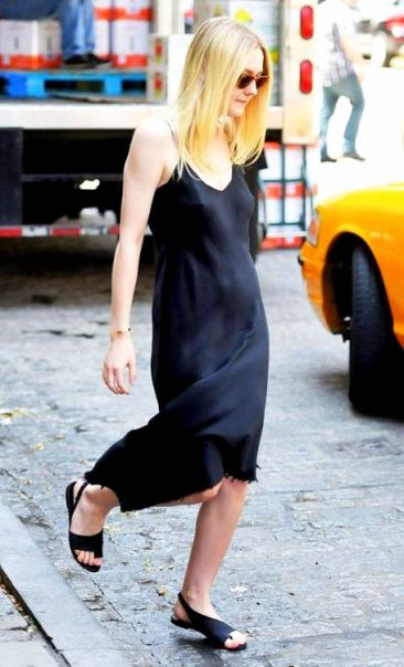 Dakota Fanning wears a black slip dress, flat leather sandals, and Ray-Ban clubmaster sunglasses
